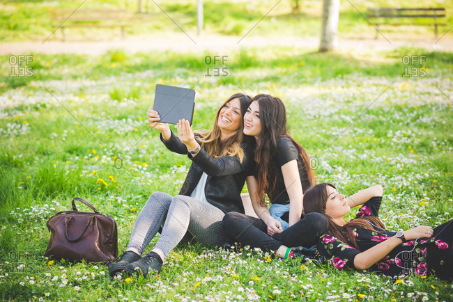 Young female friends sitting in park taking digital tablet selfie