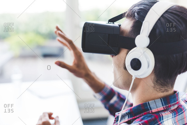 Young male designer testing virtual reality headset in office