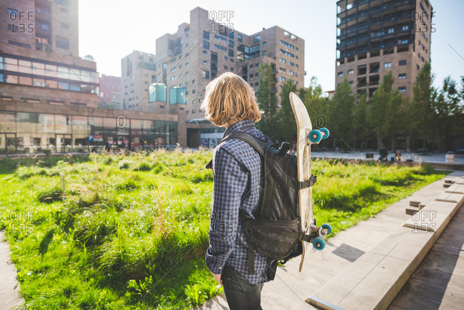 Young male urban skateboarder carrying backpack with skateboard