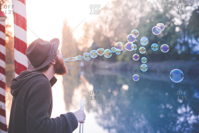 Young man blowing bubbles