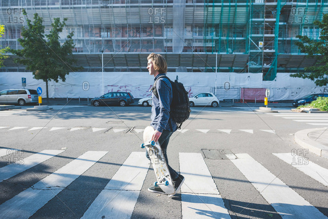 Young man crossing pedestrian crossing with skateboard