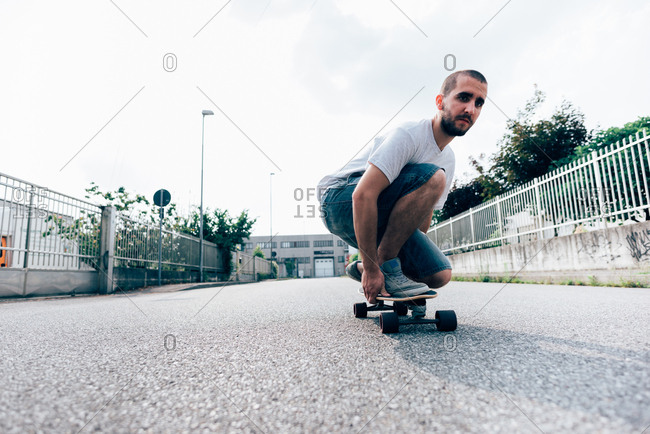 Young man crouched on skateboard