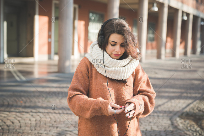 Young woman examining headphone cable on street