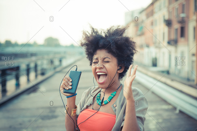 Young woman screaming to music from smartphone in city
