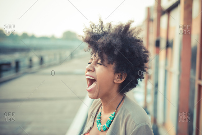 Young woman screaming laughter in city