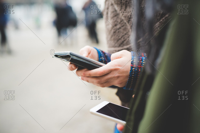 Young woman using smartphone outdoors, mid section