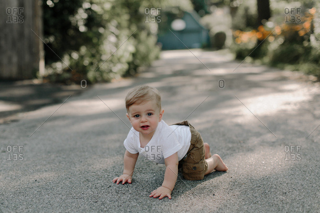 Toddler boy crawling in the driveway