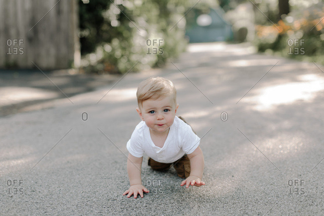 Portrait of toddler boy crawling in the driveway