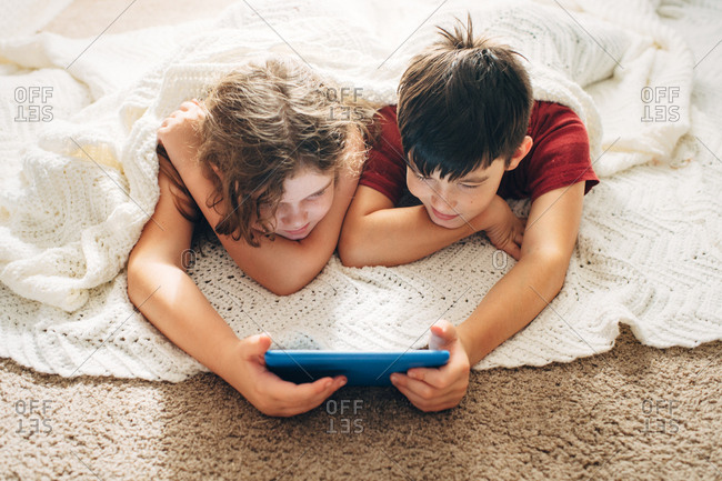 Brother and sister looking at tablet together while lying on floor under a blanket