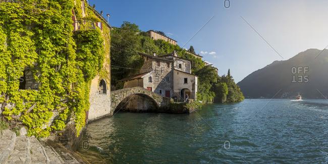 Nesso, Italy - April 29, 2017: Lake Como, Como province, Panoramic view of the lake shore and the roman stone bridge
