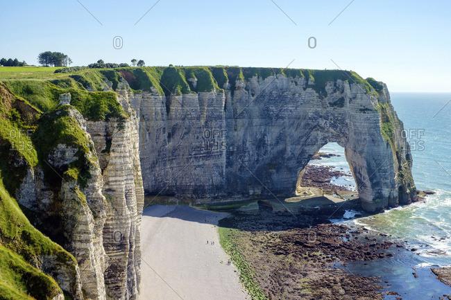 France, Normandy (Normandie), Seine-Maritime department, Etretat. White chalk cliffs and Aiguille d'Etretat, natural stone arch on the coast