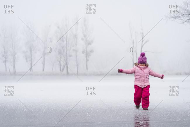 Little girl having some winter fun on the frozen lake