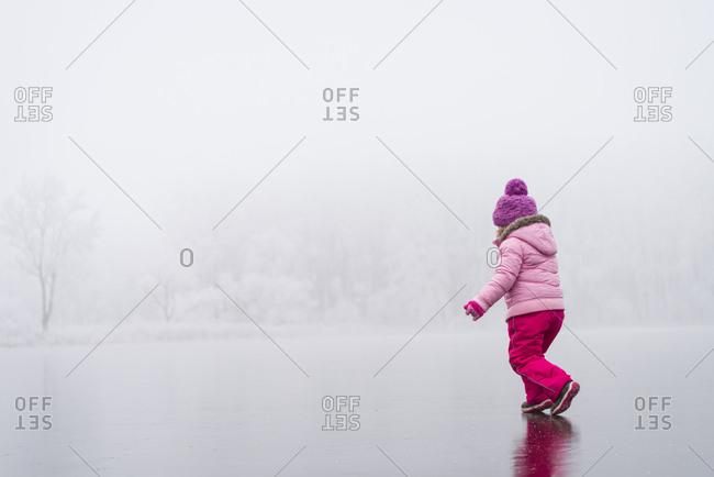Little girl in winter wear walking carefully on iced lake