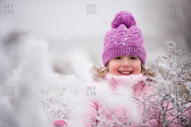 Cheerful girl child in winter wear enjoying outdoors