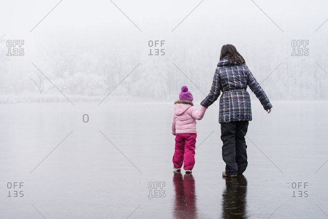 Mother and daughter on frozen lake, rear shot