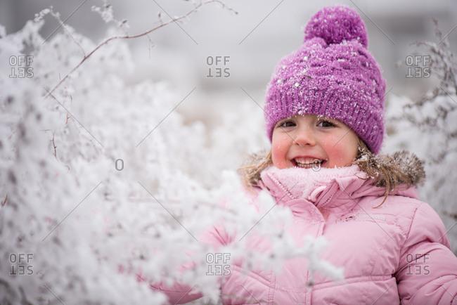 Girl child having fun in winter park during snowfall