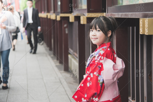 Beautiful Asian girl wearing red kimono walking in the Tokyo Japan.