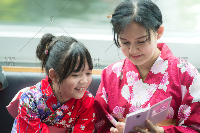 Asian girl and her mother smiling while looking at a phone