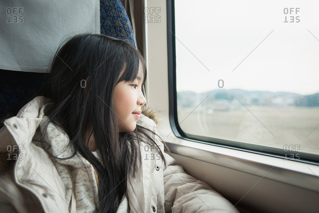 Little Asian girl looking through a train window