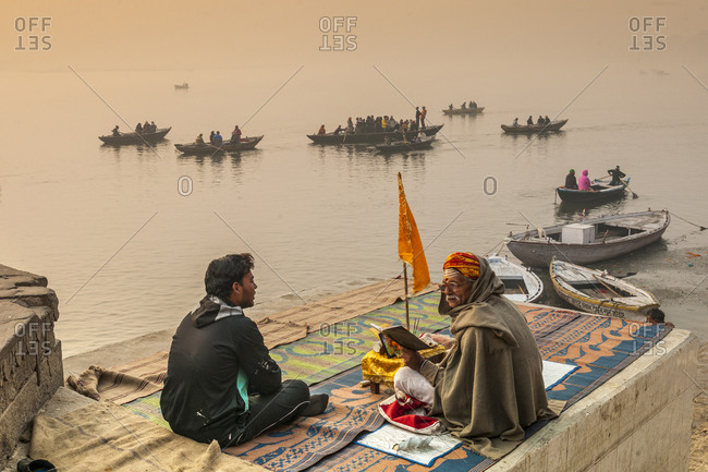 Varanasi, India - January 30, 2013: Holy man and his follower talking at Munshi Gath