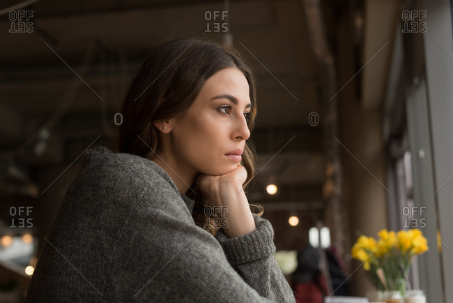 Close up of thoughtful woman with hand on chin in cafe