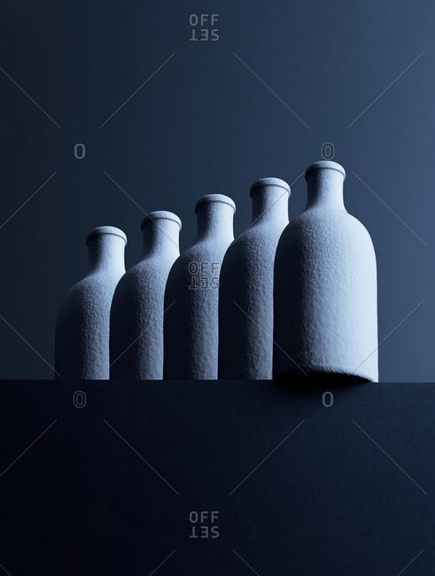 Row of five bottles in front of dark background- 3D-Rendering