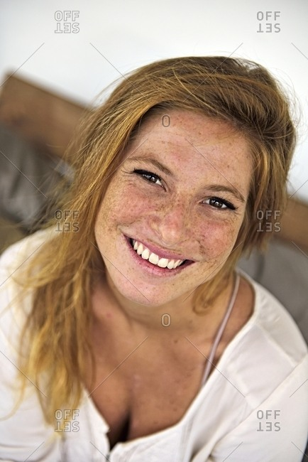 Portrait of laughing strawberry blonde young woman with freckles