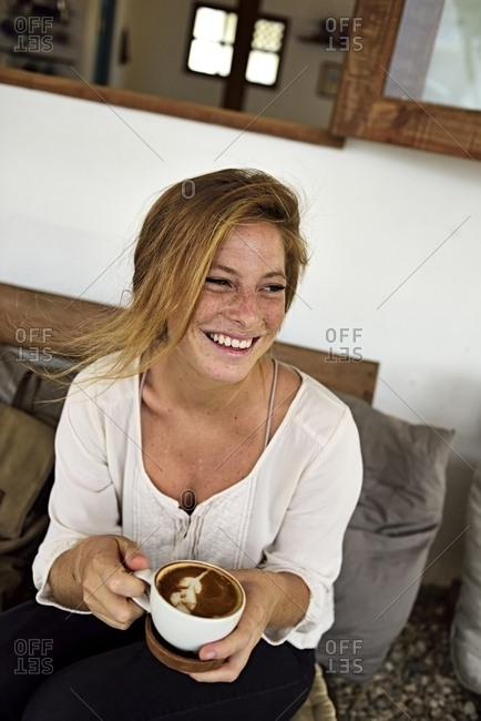 Portrait of laughing strawberry blonde young woman with cup of coffee