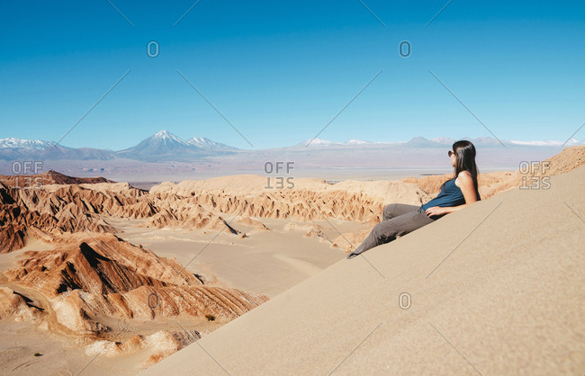 Chile- Atacama Desert- woman sitting on dune looking at view