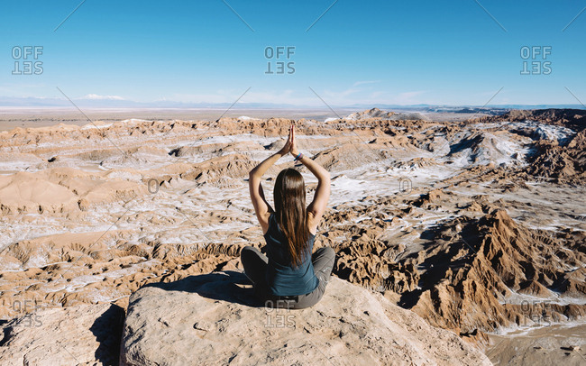 Chile- Atacama Desert- back view of woman practicing yoga on a rock