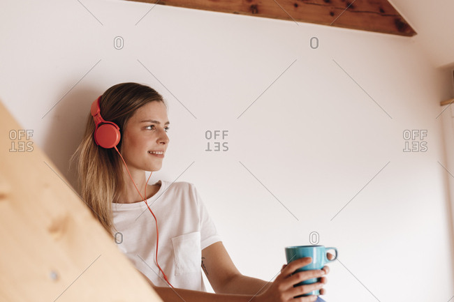 Young woman relaxing at home with a cup of tea- listening music