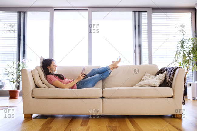 Young woman lying on couch using tablet for video chat at home