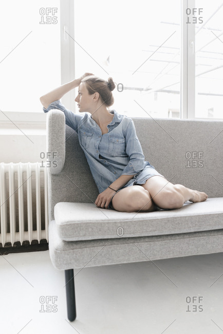 Woman sitting on couch in a loft looking out of window