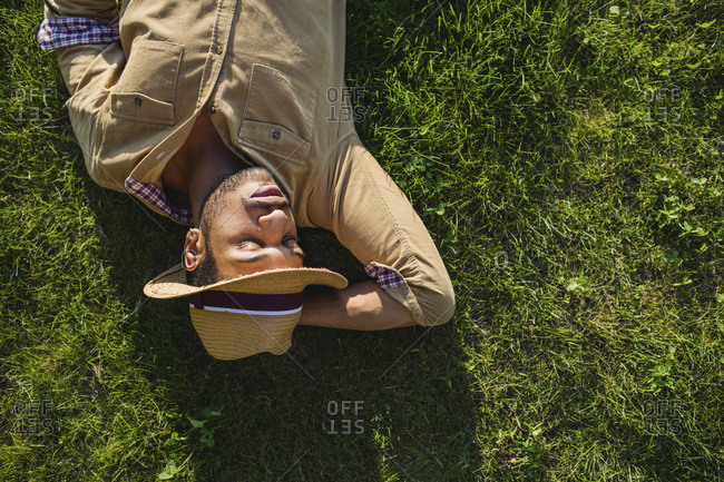 Young man sleeping on a meadow- top view
