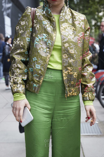 London, England - June 11, 2017: Woman wearing green trousers and gold patterned jacket