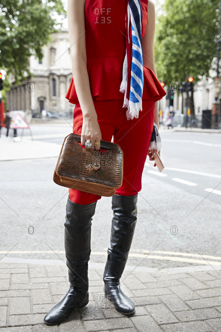 London, England - June 11, 2017: Woman in red top and trousers with a brown handbag, vertical