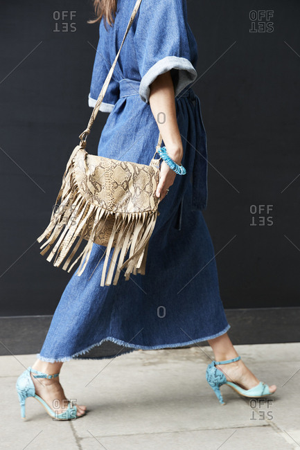London, England - June 11, 2017: Low section of a woman in boho denim dress and fringed bag