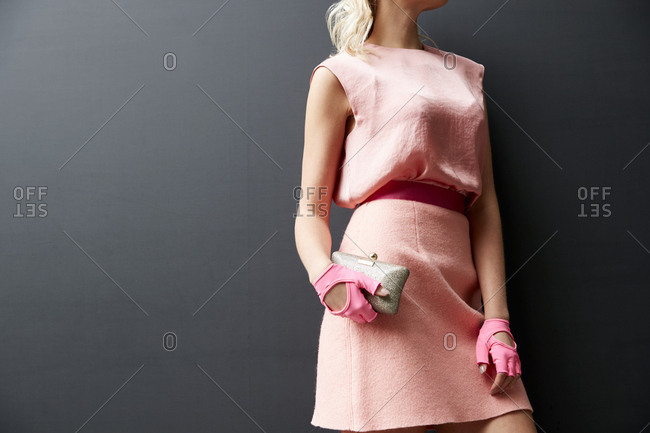 London, England - June 11, 2017: Woman in pink dress, pink belt and pink gloves holding purse