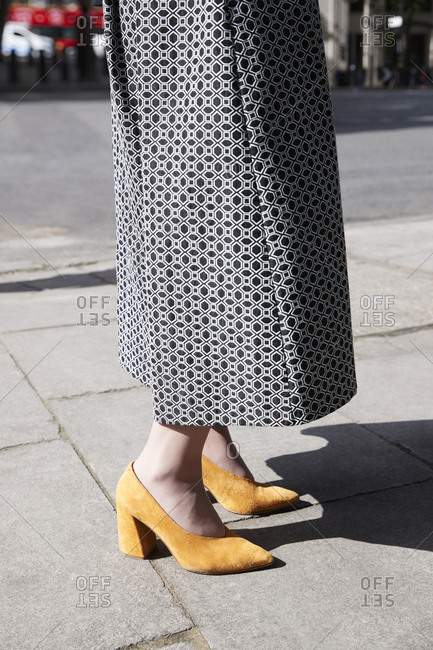 London, England - June 11, 2017: Low section of a woman wearing a maxi skirt and yellow shoes