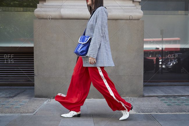 London, England - June 11, 2017: Woman in red trousers and grey jacket walking, side view