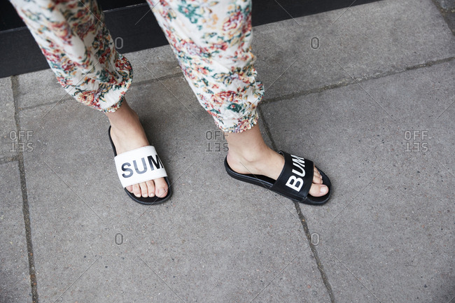 London, England - June 11, 2017: Low section of woman in floral trousers and black and white slippers