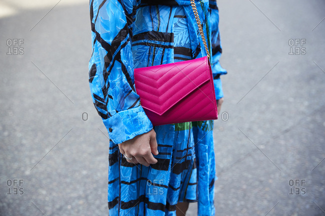 London, England - June 11, 2017: Mid section of a woman in blue dress with pink leather bag