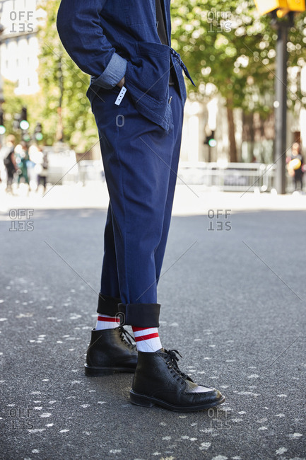 London, England - June 11, 2017: Low section vertical of man in blue trousers and black boots