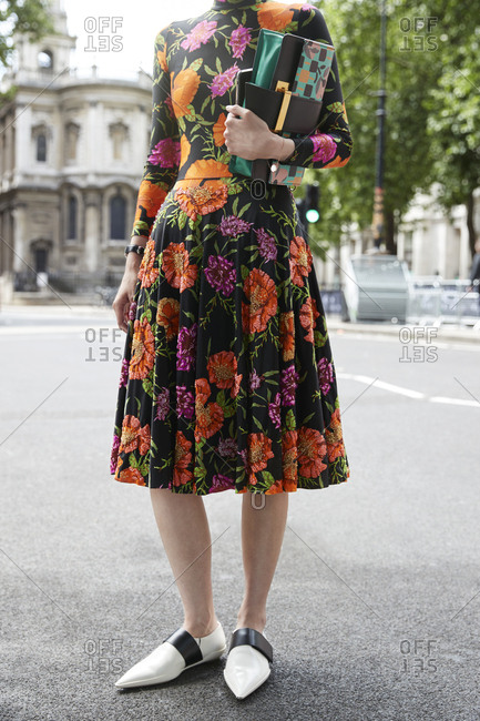 London, England - June 11, 2017: Woman in floral dress and white shoes, low section