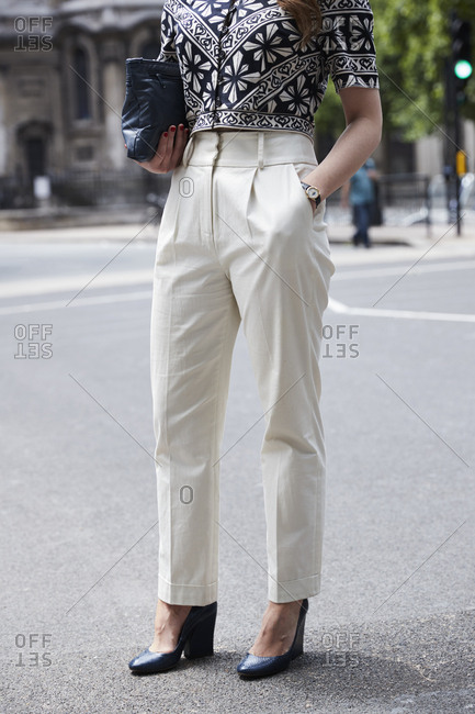 London, England - June 11, 2017: Woman in black and white top and white trousers, low section
