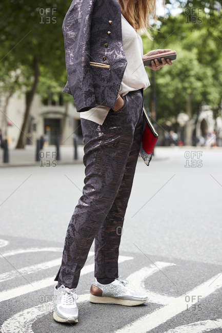 London, England - June 11, 2017: Woman in shiny patterned suit using smartphone in street