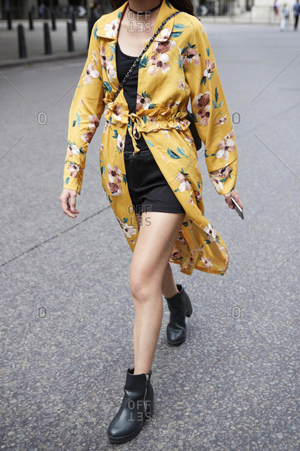 London, England - June 11, 2017: Woman in minidress and mustard floral gown walking in street