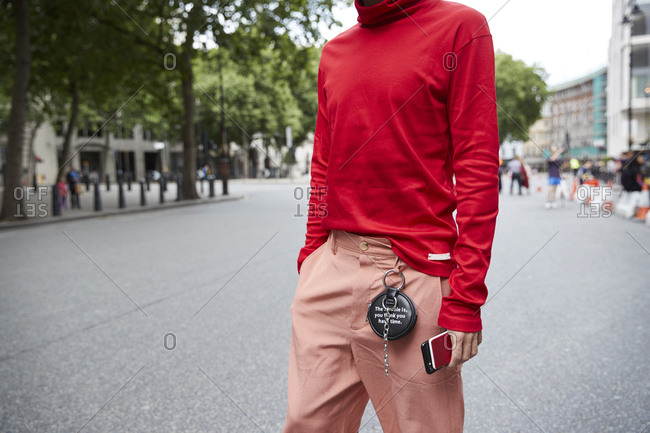 London, England - June 11, 2017: Mid section of man in red polo neck top and pink trousers