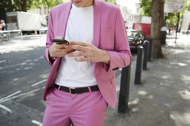 London, England - June 11, 2017: Mid section of man in baby pink suit using phone in street