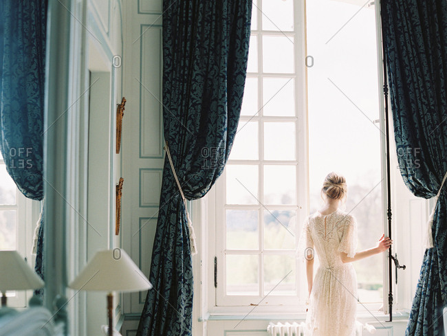 Woman in lace dress by window